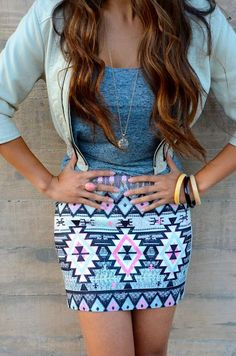 Lightweight tank under a beige-color leather jacket over a tribal print skirt.