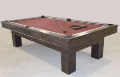Billiard table with enclosed pockets, built from distressed knotty alder, with matching custom wrought iron bridge and ball triangle.