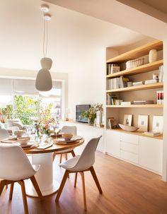 Salón-comedor con mesa redonda, sillas de diseño, mueble de salón con baldas hasta el techo en blanco y madera clara_429281