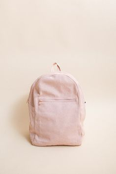 Baggu Zip Backpack. An everyday canvas backpack in a pretty pastel shell pink color. - 10.5 in. W x 15.5 in. H x 6 in. D. - Interior sleeve holds a 13 inch MacBook - Front zip pocket - Adjustable stra