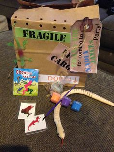 Reptile party goody bags! Contents include: growing reptile, wooden snake, paint, and paintbrush, hatching reptile egg soap, glow-in-the-dark rubber lizard, and 2 reptile tattoos!