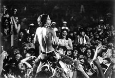 Iggy and the Stooges - the iconic peanut butter smearing image, Iggy aloft on a sea of hands.