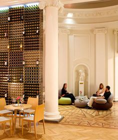 """Le Bar à Vin du CIVB (Bordeaux). """"Bordeaux fusty and overpriced? Not at this bar run by the region's wine council. Architect Françoise Bousquet has appointed the soaring Neoclassical space with whimsical pebble-shaped chairs and original artwork, including a grape-themed Aubusson tapestry."""""""