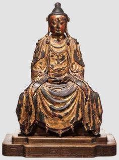 A Chinese gilt-bronze figure of Guanyin, Ming period Bronze with remnants of gilt lacquer. Portrayal of the seated Guanyin with necklace, the removable tiara missing. The flowing robes loosely draped over the base. On later base of carved hardwood. Height without base 44.5 cm, total height 50 cm.