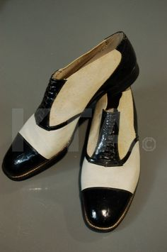 A rare pair of stylish Giuseppe Marini co-respondent shoes, Italian, 1920s, stamped to the interior G.Marini, Milano, of black patent and white suede leather with elasticated uppers to each side of patent faux laced panel, 28cm long, approx size 8, (2) Giuseppe Marini founded his bespoke shoe-making business in Rome in 1899.