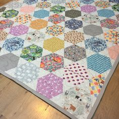 Hexagon quilt, machine pieced large hexies set in rows with triangles. Rosalie quilt pattern.