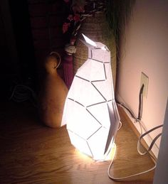 Make your own penguin lamp from paper or card stock and simple bits from the hardware store using this PDF template! This cute penguin lamp adds an adorable bit of decor to any room and lights up a corner with a stained glass-like frame. Its a great piece for adding character to a