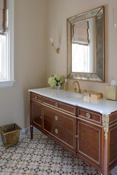 A gold beveled washstand mirror is flanked by brass sconces mounted on beige walls above a French footed washstand accented with a gold trim and a marble countertop finished with an undermount round sink paired with an antique gold gooseneck faucet. French Bathroom, Beige Bathroom, Hall Bathroom, Bathroom Floor Tiles, Family Bathroom, Basement Bathroom, Bathroom Vanities, Bathroom Ideas, Sink Countertop