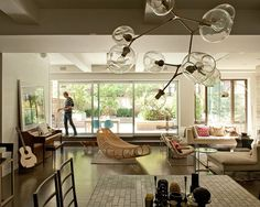 #Modern living room #design with a funky #light fixture and gorgeous #rattan #lounger