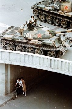 From the book China, Portrait of a Country by Liu Heung Shing    On June 5, 1989, a young couple waits beneath Jianguomenwai bridge on the fringe of Beijing?s diplomatic area, as PLA tanks roll above them. Martial law had been in place since the end of May. Liu Heung Shing, 1989.
