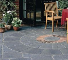 Stonemarket Millstone centre stone 465mm red brick insert creates an attractive contrast with the blue grey colour of this paving circle. #PavingCircles #DecorativePavingCircles