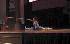 Anna cartwheels and lands in the splits with her spear at a performance. From NZ Wushu, from Auckland, New Zealand. Chinese Martial Arts, Cartwheel, Auckland, Kung Fu, Stage, Anna, Scene