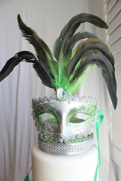 "Over The Top Cake Topper offers a unique variety of unusual, custom cake toppers for any type of party, Wedding, Quinceanera, Sweet Sixteen, birthday, graduation, New Year's, Ball and all other celebrations and themes!  A Green and Silver glittery masquerade mask sits on an elegant silver rhinestone base. The green and black feathers along with the silver sparkle give the perfect chic finish.  The topper sits on a base 5"" diameter silver and rhinestone base. This base is attached to a…"