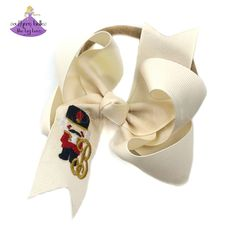 Looking for a nutcracker gift for baby girl? Our beautiful Christmas baby bow headband is personalized and perfect for nutcracker enthusiasts. It features an embroidered nutcracker with the initial letter of your choice. Available in two sizes and a variety of colors, it is the perfect holiday accessory. It has been beautifully crafted out of quality ribbon that is slightly twisted for that classic boutique bow shape that won't lie too flat when worn. Baby Girl Headbands, Elastic Headbands, Baby Girl Gifts, Baby Bows, Glitter Ribbon, Gold Glitter, Christmas Hair Bows, Christmas Accessories, Boutique Bows