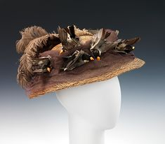 Hat- At this time, hats were lavishly trimmed and possibly adorned with cotton flowers, leaves, crushed fabric, stuffed birds and various feathers. This particular hat uses woven bast fiber that brings to mind a bird's nest. The design illustrates the popularity of using real birds as millinery trim.  Date: ca. 1890 Culture: American Medium: bast fiber, cotton, birds, feathers