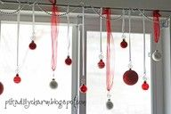 Hang Christmas decorations with pretty ribbons from a curtain rod.  I have pinned a similar idea with candy canes.
