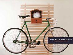 """Este es el estante de bicicletas en forma de casa de pájaros de Lauren Thomas y Jennifer Karaem de Dimini. Los diseñadores escriben:  """"Se monta fácilmente en la pared y de forma segura, ofreciendo una solución de almacenaje puertas adentro muy innovadora para tu bicicleta y casco. Hecho de contrachapado de madera y terminado a mano con cera de abejas no tóxica y aceite de linaza, esta pieza aliviará la carga de almacenaje e iluminará tu hogar""""."""