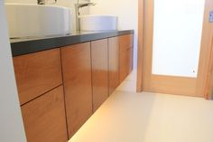 Modern bathroom with wood cabinets, above counter sinks
