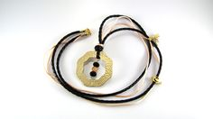 Necklace made of black braided leather and warm pink cord. At the bottom of the necklace there is a golden circle with glass beads on the inside. From the braided leather there hang a golden Eiffel Tower pendant, a glass bead and a golden clef.