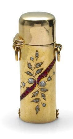 A diamond, ruby and eighteen karat gold lipstick holder  with French assay mark; weighing approximately: 23.1 grams; dimensions: 2 1/16 x 15/16 x 1/2in.