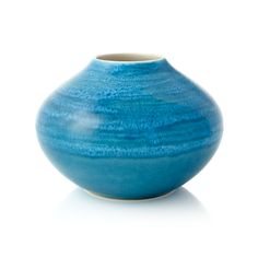 Reactive glaze cascades ribbons of uniquely patterned blue on a low vase, handcrafted with a modern curved shape. CeramicReactive glazeHand washMade in Portugal.