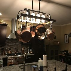Clear seedy glass adds to the industrial inspired look of this bronze pot rack chandelier. 36 wide x deep x 20 high. Canopy is 13 wide x 4 deep x 2 high. Style # at Lamps Plus. Pot Rack Hanging, Hanging Pots, Pan Hanger, Kitchen Island Furniture, Pot Storage, Rustic Italian, Rustic Wall Clocks, Tuscan House, Bronze