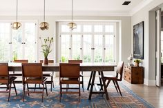 "A 13-foot-long farm table from Obsolete, paired with midcentury Brazilian chairs from Thomas Hayes Gallery, sits atop a reproduction Khotan rug from Lawrence of La Brea in the dining room. Smoky-glass pendant lights handpicked by Hall from Lawson-Fenning complete the look. ""You wouldn't expect something so modern and shiny to work with these warm pieces, but the contrast is really nice,"" says Perera."