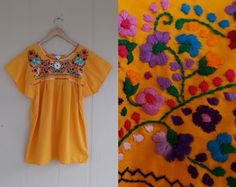 This vintage mexican peasant blouse features floral embroidery in a rainbow of colors across the chest.
