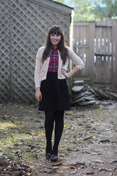 tick tock vintage. plaid button up with a cardi over it, black skirt and black tights.