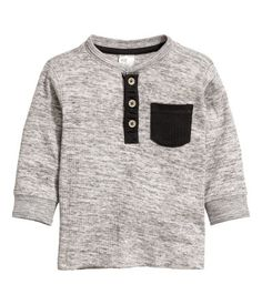 Gray melange. Long-sleeved henley shirt in soft, ribbed cotton jersey. Button placket, chest pocket, and ribbing at neckline and cuffs.