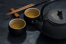 Asian style, cup and teapot with green tea
