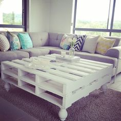 Sectional w/ awesome pillows and white pallet coffee table adding the fancy legs to the pallets makes it look pretty!