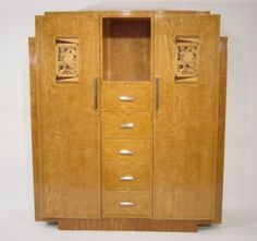 Cabinet, France, c. 1930. Ash-veneered cabinet on a reeded base with five drawers, a central open shelf and two swing doors with marquetry in different precious woods; nickel-plated metal fittings.