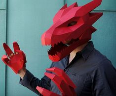 Become a fire breathing monster this Halloween when you construct one of these paper dragon masks. This easy to craft wearable mask can be completed in a few short hours by using a printer, scissors, cardboard, and some adhesive materials.