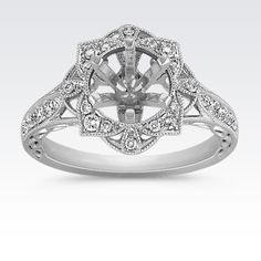 This darling vintage inspired floral halo engagement ring features 28 round pavé-set diamonds, at approximately .29 carat TW. The gemstones are set in quality 14 karat white gold with intricate milgrain and engraved detailing.  Simply add the center stone of your choice at approximately 1.00 carat.