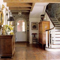 the doors, stair, exposed beams, floor, salvaged wood, stone walls, foyer, rustic wood, entryway