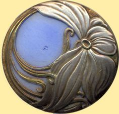 This Art Nouveau glass button is white, with an overlay of blue glass and a swirling floral design of silvered brass.