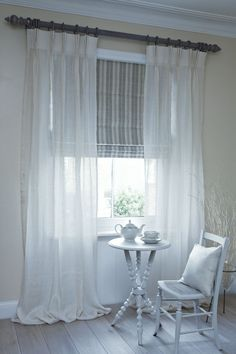 Neutral blinds and sheer curtains gives the room a soft, bright, airy feel, blending into the room rather than drawing attention to it.