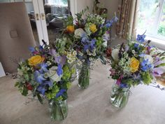 Bridal bouquets prepared ready to be top table arrangements at the reception.