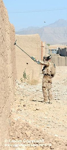 A soldier from 2 Rifles searches for Improvised Explosive Devices (IEDs) in Afghanistan.