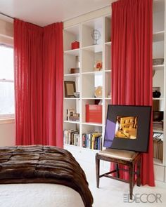 Clutter tip: Bookcases draped with sheer pop of soft cherry pink to soften room and add length