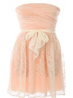 Crème Rose Dress: Features a chic strapless cut with an alluring crossover bodice, beautiful mesh cream overlay with contrast pink liner for pop, matching ribbon sash at waist, and a ravishing gathered lace skirt to finish.