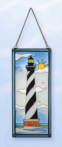 """Stain Glass Lighthouse Seabirds. Bright sunny lighthouse day at the beach scene.  Size: 17.5"""" x 7.5""""  Actual weight 2 lbs.  Photos don't do these stainglass lighthouses justice. Very crisp glass colors. They are nicer in actual appearance. Very beautiful coloring with scene of light house, clouds, seabirds and beach.  Comes complete with hangers and chain. Dress up rooms or outdoor spaces with this stained glass coastal decor piece.  Stainglass lighthouses"""