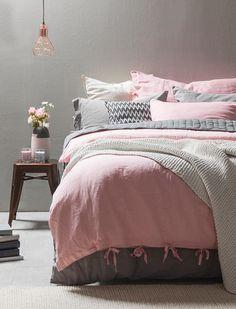 chambre romantique avec une peinture murale grise, une literie en rose et gris et un bouquet de roses