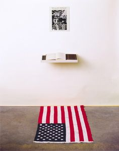 Dread Scott. What is the Proper Way to Display a US Flag? 1988.Silver gelatin print, US flag, book, pen, shelf, audience; 80 x 28 x 60 inches
