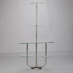 Mid Century Chrome and Glass Display Shelves  --  This circa 1950s European retail store display stand has a chrome base and frame with five glass shelves. The size and form make this a versatile and practical piece for displaying plants, artwork, pottery or other decorative objects.  --   Item:  3851  --  Retail Price:  $1495