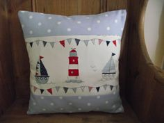 "Handmade Cushion Cover in Clarke & Clarke seaside fabric depicting boats, lighthouses and beach huts bordered with two panels of pale blue polka dot from Clarke & Clarke. The cushion measures 16"" or 40cm by 40cm but will also accommodate an 18"" pad for a fuller look. NB. Content and position of character on the fabric may be different than picture."