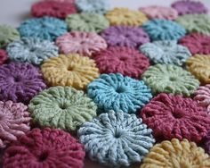 In the 1930s there was a craze for making a decorative patchwork form gathered circles of fabric, called Suffolk puffs or yo-yos. This pretty baby blanket echoes that style with ingeniously constructed, double thickness, two-round crochet puffs in pastel shades.