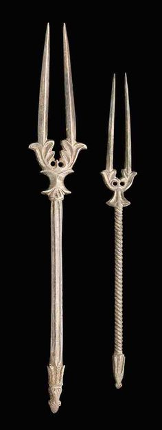 Sasanian Silver Forks, 6th-7th century CE. Two-pronged fork with stylized foliate cuff extending to a six-sided shaft with large double animal head terminal; and another similar with twisted shaft. 10¼ in. (26 cm.) and 8¼ in. (21 cm.) long respectively.