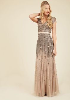 The curtains part, and you step onto the stage in this taupe gown from Adrianna Papell. The crowd hushes as the spotlights glisten off the cascading beads and sequins adorning this V-neck dress. Finessed with cap sleeves, a satin waistband, and unbelievable beauty, this dress amplifies your graceful presence!